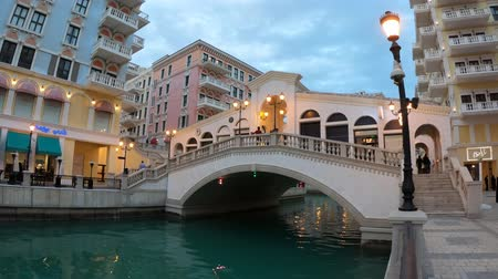 east pearl : Doha, Qatar - February 20, 2019: Rialto bridge of Doha in Qatar. Venice at Qanat Quartier in the Pearl-Qatar, Persian Gulf, Middle East. Famous tourist attraction at sunset. Travel in Qatar.