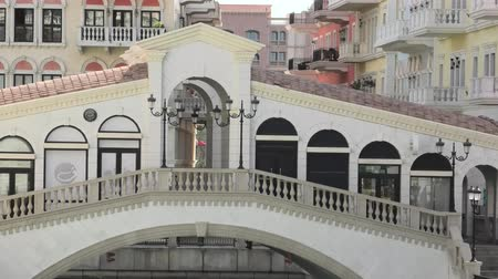 east pearl : Doha, Qatar - February 20, 2019: zoom out from Venetian Rialto bridge on canals of picturesque and luxurious district of Doha, Qatar. Venice at Qanat Quartier in Pearl-Qatar, Persian Gulf, Middle East