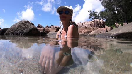 águas : La Digue, Anse Caiman, natural swimming pool. Split view of blonde woman underwater on crystal calm waters of remote Anse Caiman with fishes. Secret beach at Seychelles. Scissortail sergeant fishes.