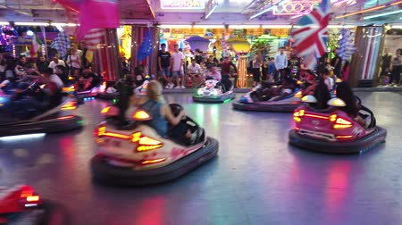 bolognai : Province of Bologna, Italy - June 8, 2019: Children and young people playing driving crazy dodgem cars in the Amusement Park night arena. Cars with European contries flags.
