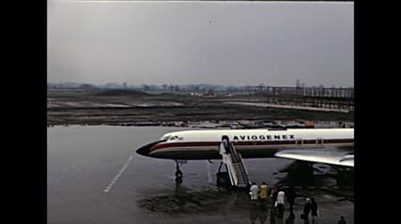 70年代 : TENERIFE, SPAIN - CIRCA 1976: Aviogenex airline boarding airplane with tourists and departing taking off from Tenerife Norte Airport. Historical archival of Tenerife island of Spain in Africa in 1970s