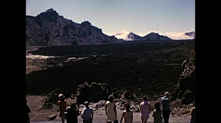 seventy : TENERIFE, SPAIN - CIRCA 1976: group of tourists in vintage dress visiting lava stone of Teide Volcano in Teide National Park. Historical archival of Tenerife island of Spain in Africa in 1970s Stock Footage