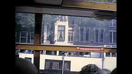seventy : Sea view of Amsterdam homes architecture and street by boat tour in Holland. Historical archival Amsterdam touristic cruise in the capital city of Netherlands in the 1970s.