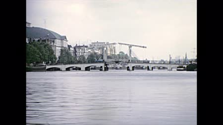 seventy : Sea view of Amsterdam bridges in 70s by boat tour in Amsterdam town of Holland. Historical archival touristic cruise in the capital city of Netherlands in the 1970s.