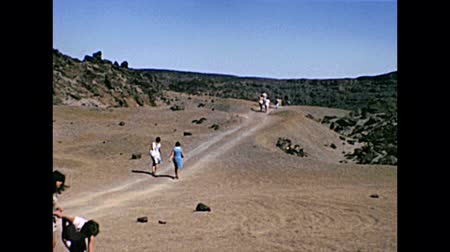 kanarya : TENERIFE, SPAIN - CIRCA 1976: group of tourists in vintage dress climbing the Teide Volcano mountain in Teide National Park. Historical archival of Tenerife island of Spain in Africa in 1970s