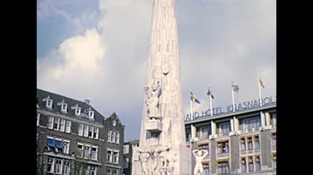 gát : AMSTERDAM, HOLLAND - CIRCA 1976: National Monument of Amsterdam in Dam square with people in the centre of the city. Historical archival in Amsterdam capital city of Netherlands in 1970s. Stock mozgókép