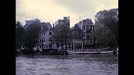 アムステルダム : AMSTERDAM, HOLLAND - CIRCA 1976: sea view of historical buildings, towers and hotels of Amsterdam. Archival Boat Tour Cruise in capital city of Netherlands in 1970s.