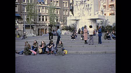 seventy : AMSTERDAM, HOLLAND - CIRCA 1976: young white and black people in vintage dress sitting in Dam square in the centre of the city. Historical archival of Amsterdam capital city of Netherlands in 1970s.