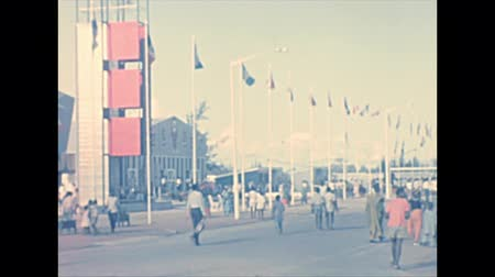 lagos : LAGOS, NIGERIA, AFRICA - circa November 1977: Flag of the countries of the world at Nigerian International Trade Fair with black people visitors. Historical archival of Nigeria of Africa in 1970s. Stock Footage