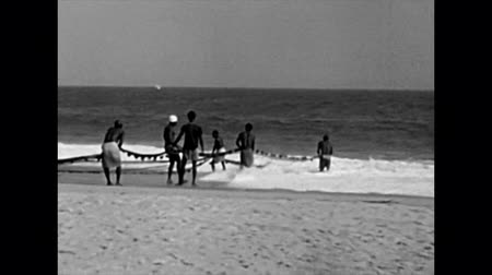 lagos : LAGOS, NIGERIA, AFRICA - circa 1977: Black fishermen fishing with a fish net on the beach on Guinea Gulf in Lagos City. Historical archival of Nigeria state of Africa in 1970s.