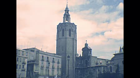 archief : VALENCIA, SPAIN - CIRCA 1970: the bell tower of the Valencia Cathedral in square Placa de la Reina. People in vintage dress and vintage cars on the road. Archival of Valencia city of Spain in 1970s.
