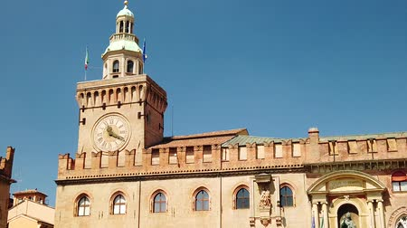 bolognai : SLOW MOTION: clock tower of Palazzo dAccursio or Comunale overlooking Piazza Maggiore, today the seat of the municipality of Bologna in Italy. Stock mozgókép