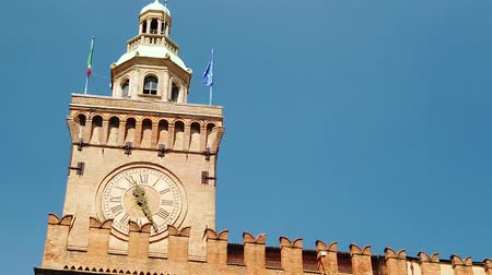 palazzo : Close up of Accursi tower is also known as the Clock Tower of Palazzo dAccursio or Comunale, Piazza Maggiore, Bologne in Italy in the blue sky. SLOW MOTION