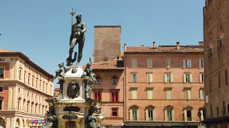 bolognai : Architecture panorama of Bologna city in Emilia region of Italy. Neptune bronze statue and restored fountain, with historic orange-red buildings background in Nettuno square of town center SLOW MOTION Stock mozgókép