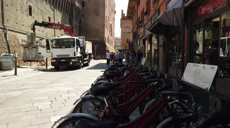 中世の : Bologna, Italy - June 24, 2019: Bologna red city bikes in front of walls of the historical Accursio palace. 動画素材