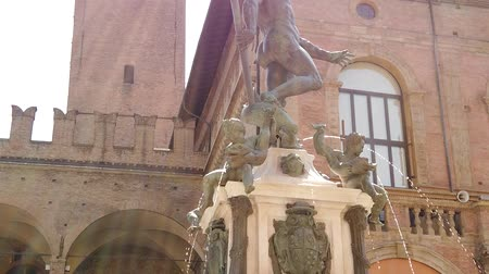 bolognai : SLOW MOTION sun rays on Bologna Neptune statue-fountain of Bologna city in Italy. Restored in 2018 and located in Nettuno square of Bologna city center. Lower ground view with blue sky.