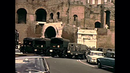 цыган : ROME, ITALY - CIRCA 1970: car traffic and military Italian army trucks at Porta Pinciana door of the city of Rome, piazza Brasile square. Historical archival of Rome capital of Italy in the 1970s.