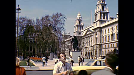 standbeeld : LONDON, ENGLAND, UNITED KINGDOM - CIRCA 1970: historical palace, Government Offices in Great George Street of London, beside Westminster Palace. Winston Churchill Statue. Archival of England in 1970s. Stockvideo