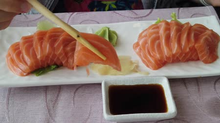 酒 : Slow motion on glamour woman eating salmon sashimi with chopsticks. In Japanese Asian fusion restaurant. Healthy food, light diet concept. Happy woman eating japanese food. healthy diet of fresh food.