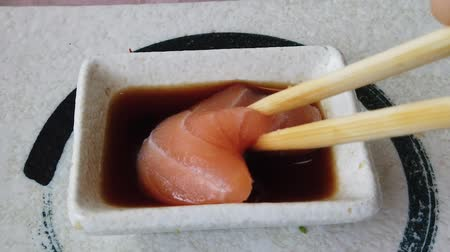 酒 : Slow motion of salmon sashimi in deeped in soy sauce bowl with chopstick. Japanese fusion food, Asian cultures. Healthy food, light diet concept. 動画素材