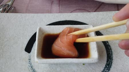 酒 : SLOW MOTION: Sushi of salmon fillet in soy sauce bowl by chopsticks. Japanese fusion food, Asian cultures. Healthy food, light diet concept. Slow motion closeup feeding.