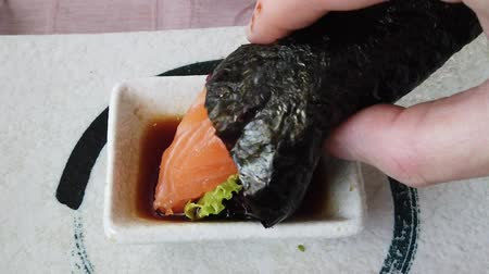 fumado : SLOW MOTION: focused hand putting a California Temaki cone with brown rice, avocado and seaweed, deeped into soy sauce bowl. Japanese fusion food, Asian cultures. Healthy food, light diet concept.
