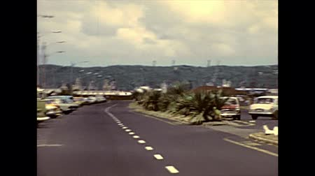 super car : DURBAN, South Africa - 1981: street view with vintage cars on the Durban highway by Durban Beach waterfront with old lighthouse. Historical archival footage in Durban city of 1980s in South Africa. Stock Footage