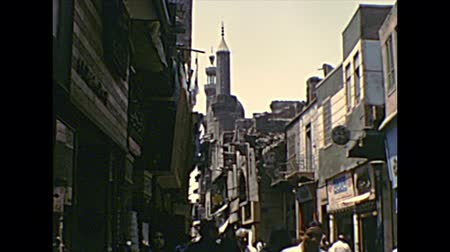 khalili : CAIRO, EGYPT, AFRICA - circa 1973: Khan Al-Khalili Bazaar with Egyptian people in a traditional dress and mosque minaret. Historical archival of Cairo capital city of Egypt in the 1970s. Stock Footage