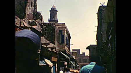 archief : CAIRO, EGYPT, AFRICA - circa 1973: Khan Al-Khalili Bazaar with local Egyptian people in a traditional Arab dress and mosque minaret. Historical archival of Cairo capital city of Egypt in the 1970s.
