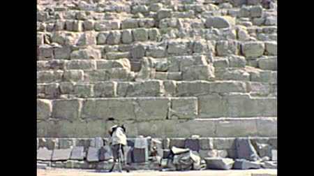 archeological : CAIRO, GIZA, EGYPT, AFRICA - circa 1973: Egyptian Bedouin men on camels at the Great Giza Pyramid of Khafre. Valley Temple of Khafre. Historical archival of Cairo of Egypt in 1970s