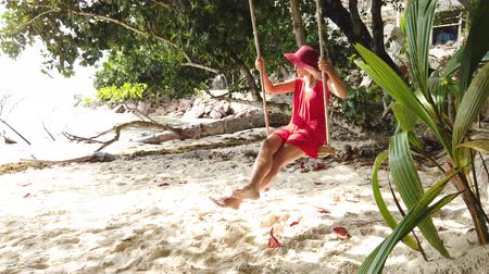 sunhat : Happy lifestyle tourist woman in red dress swinging on tropical beach under coconut palm trees with a fruit drink. Summer tropical holiday destination. Anse Severe, La Digue, Seychelles, Indian Ocean. Stock Footage