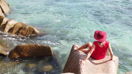 anse : SLOW MOTION: Happy tourist woman in red dress looking Anse Severe Beach from granite blouder stones. La Digue, Seychelles, Indian Ocean. Female lifestyle enjoying summer holidays at tropics. Stock Footage