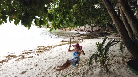 sunhat : Elegant tourist woman with wide hat sitting on swing under tropical trees and looking at sea of Anse Severe in La Digue, Seychelles, Indian Ocean. Lifestyle female enjoying in summer holidays.