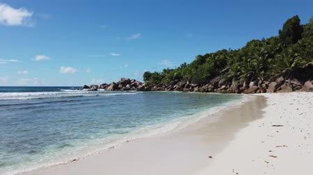 la digue island : White sandy beach and turquoise clear sea of Anse Cocos can be reached with a trek starting from Grand Anse and passing through Petite Anse. Peaceful wallpaper of tropical Seychelles beach, La Digue. Stock Footage