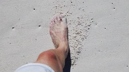 anse : SLOW MOTION: man feet walking on the white sandy beach of Anse Cocos, a Seychelles beach of La Digue island. Footprints in the sand in slow motion.