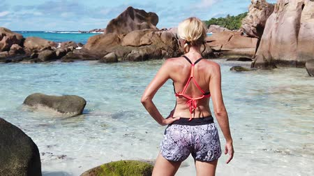 anse : SLOW MOTION: Blonde tourist woman in bikini at Anse Cocos Beach with natural pool in La Digue, Indian Ocean. Young girl enjoying. Peaceful tropical Seychelles.