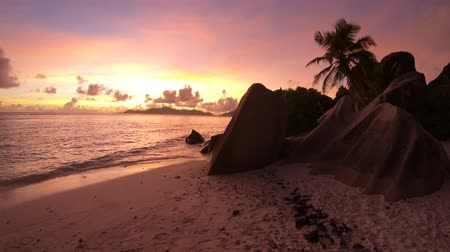 żródło : shoreline near shaped granite stones of Anse Source dArgent with sunset sky. Seychelles honeymoon. Sunlight over the sea on the horizon in La Digue, Seychelles. Wideo