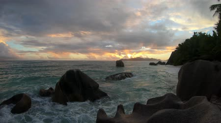 anse : Seychelles, La Digue, Anse Source dArgent at sunset. Landscape with sky and colorful clouds on rock stone of granite with palm trees. Sun at twilight on the calm sea on the horizon.