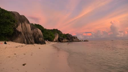 żródło : Seychelles, La Digue, Anse Source dArgent at twilight. Landscape of colorful clouds in the sky on rock stone of granite boulder. Calm and tranquil sea on the horizon.