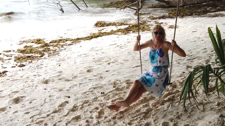 sunhat : SLOW MOTION: Elegant tourist woman with blue dress on swing under tropical trees and enjoying the beach Anse Severe in La Digue, Seychelles, Indian Ocean. Lifestyle female in summer holidays.