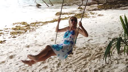 anse : Pretty tourist woman sitting on swing under tropical trees of Anse Severe in La Digue, Seychelles, Indian Ocean. Lifestyle female enjoying in summer holidays. SLOW MOTION