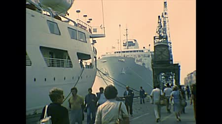 docked : Venice, Italy - circa 1980: cruise boats docked on the pier of Venezia harbor with tourists on a tour of Venetian lagoon. Archival of Venezia city of Italy in the 1980s.