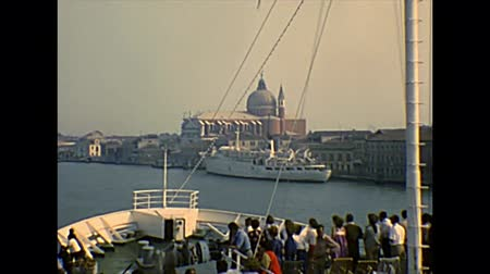 docked : Venice, Italy - circa 1980: Giudecca canal with big cruise ship with tourists and Santissimo Redentore church. Archival of Venezia city of Italy in the 1980s, Venetian lagoon.