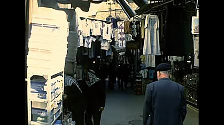 Иерусалим : JERUSALEM, ISRAEL - CIRCA 1979: road market with jewish men in black hat and men in Keffiyeh, the traditional Arab headdress worn by Palestinian men. Old city of Jerusalem archival in 1970s in Israel. Стоковые видеозаписи