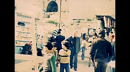 zsidó : JERUSALEM, ISRAEL - CIRCA 1979: tourists and Israeli people at Damascus Gate of the wall of Old Jerusalem City. Historic archival footage of Israel in the 1970s.
