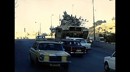 damasco : JERUSALEM, ISRAEL - CIRCA 1979: Israeli tank in Jerusalem streets around the old city with vintage cars in Damascus Gate area. Historic archival footage of Israel in the 1970s.