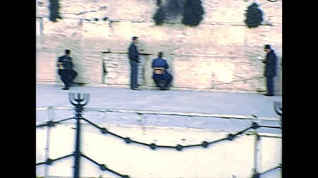 wailing : JERUSALEM, ISRAEL - CIRCA 1979: Jewish men in typical black dress and hat praying against the Western Wall in Old City of Jerusalem. Historic archival footage of Israel in the 1970s.
