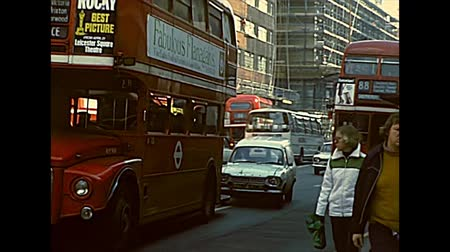 archief : LONDON, UNITED KINGDOM - CIRCA 1977: vintage cars and typical double-decker red bus in Soho and Mayfair areas of Westminster City, between Oxford Street and Regent Street. Archival of London in 1970s. Stockvideo