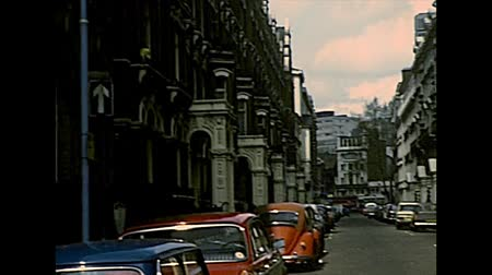 super car : LONDON, UNITED KINGDOM - CIRCA 1977: double-decker bus in Victoria st. of Westminster district with UK Government Investments building and Westminster abbey on background. Archival of London in 1970s. Stock Footage
