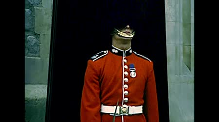 охранять : LONDON, UNITED KINGDOM - CIRCA 1977: guard of the castle Tower of London on duty in red uniform. Archival of London city of England in the 1970s. Стоковые видеозаписи